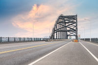 steel bridge and road with dusk sky