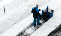 man with a snow blower clears snow from a road after a heavy snowfall