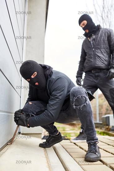 Einbrecher an Tor von Garage mit Brechstange