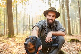 Förster mit Jagdhund und Fernglas macht Pause