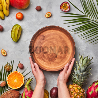 Ripe tropical fruits, coconut, mango, carambola, lychee and palm leaves on a gray concrete background. The woman's hands hold an empty brown round plate with a copy of the space. Flat lay