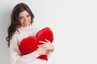 Woman with red heart shape pillow