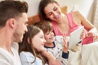 Familie und Kinder im Bett beim Video Chat