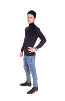 Handsome tall young man standing in jeans in the studio