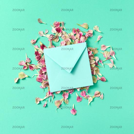Mock up craft envelope with floral petals on a turquoisebackground.