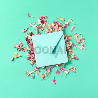 Mock up craft envelope with floral petals on a turquoisebackground.