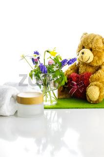 Handtücher neben einer Cremedose vor weißem Hintergrund, mit Teddybär und Blumen in einer Vase.