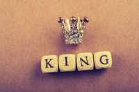 Tiny model crown beside the king wording