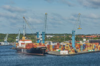 Port crane loads a container on Pier for transportation of import export and business logistic in Fr
