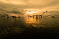 Golden light in the sky at sunrise and native fishing tool, Thailand