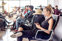 Female traveler talking on cell phone while waiting to board a plane at departure gates at asian airport terminal.
