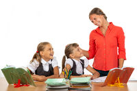 Kind teacher communicates with students sitting at a desk