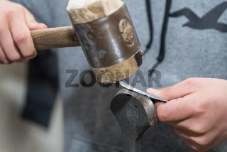 Nahaufnahme eines Handwerkers mit Holzhammer beim Biegen von Blech - Metallbearbeitung