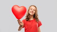 smiling teenage girl with red heart shaped balloon