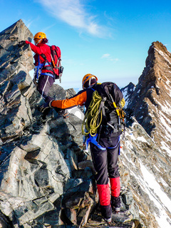 male and female mountain climber on an exposed rocky summit ridge