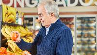 Senior beim Gemüse einkaufen im Supermarkt