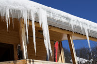 Wooden house with snow cornice and icicles on roof and ski equipment