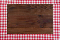 Red and white checked table runners forming a frame on a rustic dark wood table