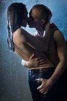 Naked couple kissing in a shower in the dark