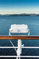 White metal exterior light fixture on railing of cruise ship, Alaska Inside Passage route.