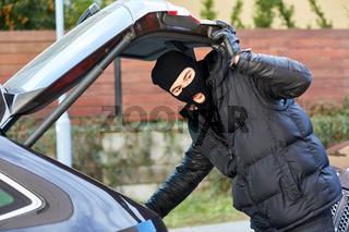Dieb mit Sturmhaube bei Auto am Kofferraum