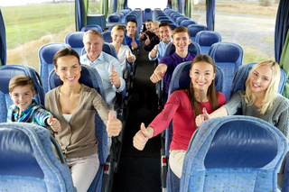 group of happy passengers travelling by bus