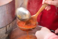 Making Tomato Sauce on the Stove. A close up of the hand mill griinding up the fresh field tomatoes to make tomato sauce.