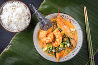Traditional Thai kaeng phet red curry with king prawns and rice as top view in a bowl on a banana leaf