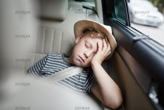 Junge mit Hut schläft auf dem Rücksitz im Auto