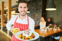 Kellner im Restaurant serviert  griechischen Salat