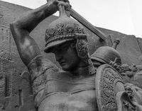 Sword in hand of warrior in armour of the medieval knight statue