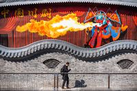 Man walking by a painted fresco of a fire spitter chinese opera artist