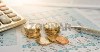 Euro coins on documents with a calculator