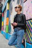 Woman using smartphone against colorful graffiti wall in New York city, USA.