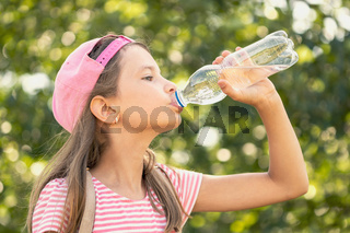 Child girl drinking water in a park