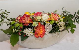 kreatives Blumengesteck in selbst gemachter Schale aus Beton - Nahaufnahme Floristik freigestellt