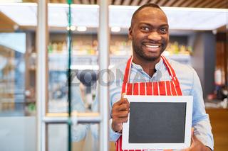 Afrikanischer Kellner mit leerer Tafel im Restaurant