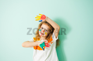 Little girl with hands and face in paint