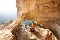 Female adventurer takes in cliff top cave views Blue Mountains