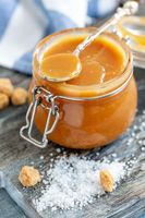 Spoon in a glass jar with salted caramel close-up.