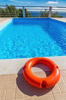 Orange life buoy lying at swimming pool