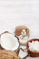 Background of coconut, coconut shell, oil in clay bowl and glass jar on white wooden table