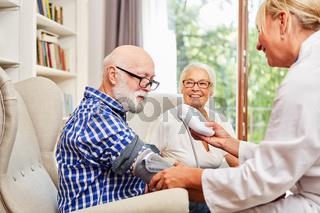 Ärztin kontrolliert den Blutdruck bei einem Senior