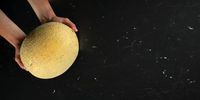Top down view, woman hands holding cantaloupe melon over black marble like board. Wide banner with space for text on right side