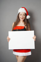 miss santa presenting blank sign with copy space