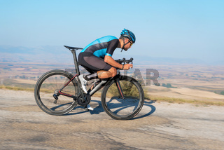 Cyclist riding the bike in the road descending the hill