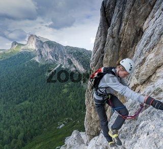 young male climber on a Via Ferrata in the Dolomites of Alta Badia with damaged and broken shoes