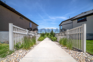 Walkway in the middle of homes with lake snow peaked mountain and sky view