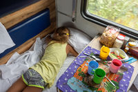Girl sleeping on the bottom shelf in the train