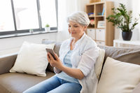 happy senior woman with smartphone at home